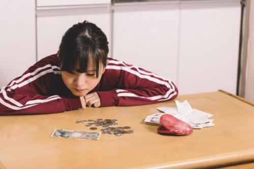 悩ましげにお金とレシートを広げて眺める女性